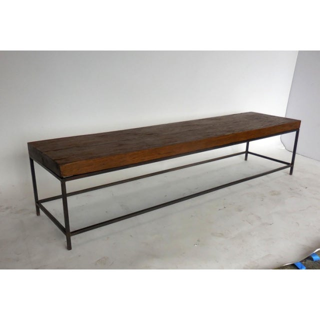 Rustic, yet modern bench or coffee table made from reclaimed wood atop and a hand-forged iron base. Can be made in any...