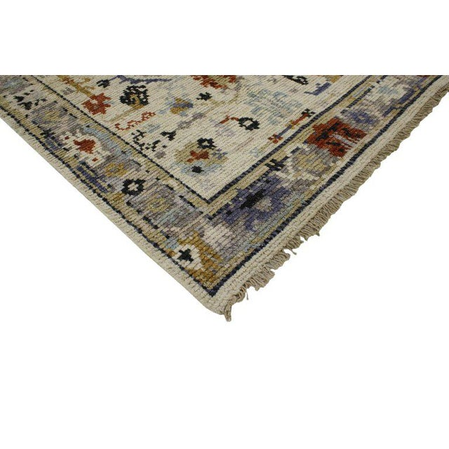 Providing elements of wanderlust and functional versatility, this modern Oushak style rug features an ivory field with...