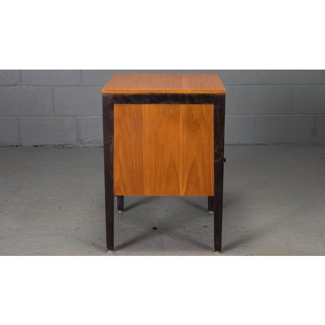 This walnut and steel cabinet designed by George Nelson for Herman Miller is constructed of a steel frame and walnut wood...