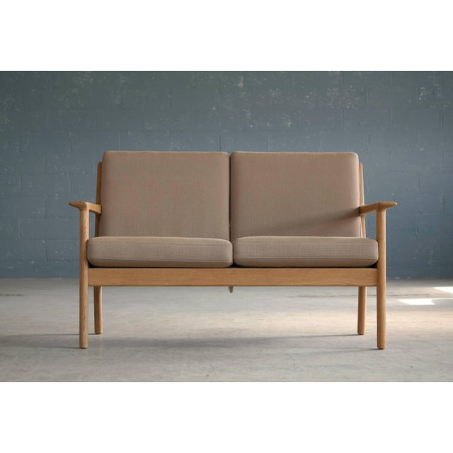 The model GE265 two-seat sofa designed by Hans J Wegner for GETAMA in the early 1970s featuring a solid oak frame and wool...