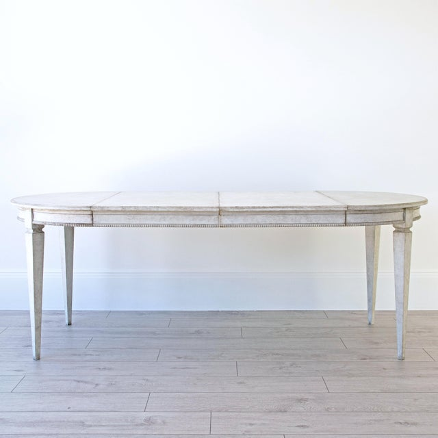 A beautiful, bespoke hand carved Gustavian extension dining table with decorative beaded apron and standing on four...