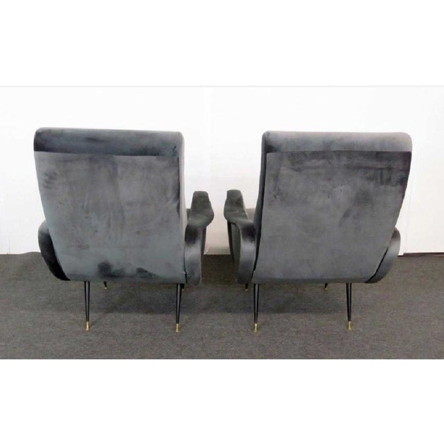 This stylishl sculpted pair of 1950s Italian modern armchairs feature tapered legs with brass tipped feet. With two back...