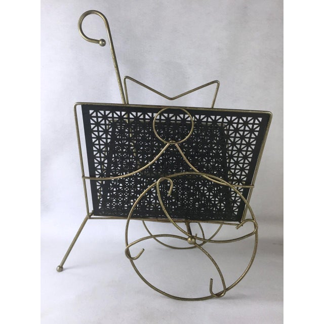 Mid-Century Modern rolling magazine rack, circa the 1960s. We love this rolling magazine cart! The black metal pieced...