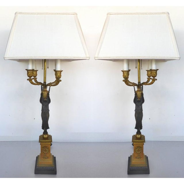 A pair of 19th century Empire bronze candelabra that have been electrified and converted to table lamps. Each has four...
