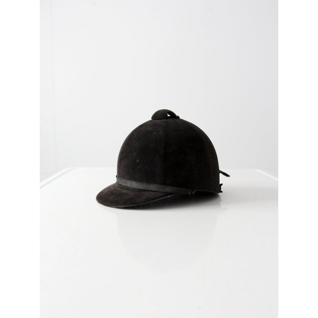 A vintage equestrian hat. The old black velveteen riding helmet has a classic short brim. The interior features an...