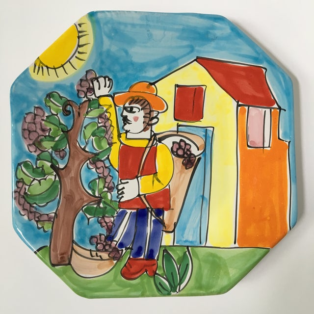 Bright and colorful wall plaque by La Musa, in Desimone style, of a farmer/vintner harvesting his grapes for wine. Larger...