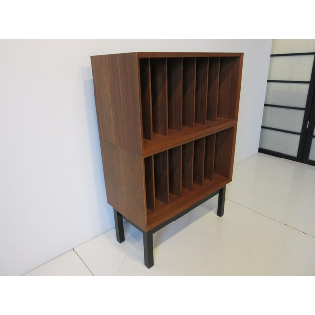 A teak wood record cabinet containing 14 slots able to hold quite a few records ( please check measurements for the number...