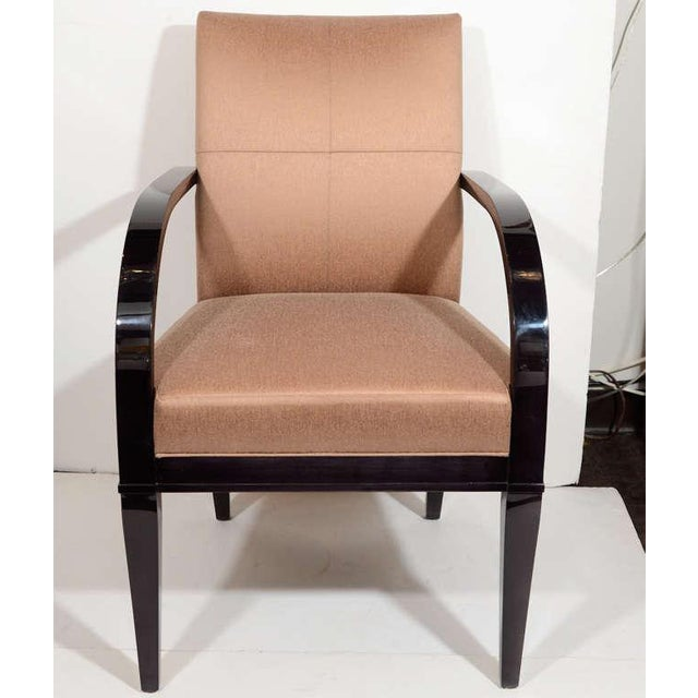 Modernist dining chair has stylized curved arm design and tapered saber legs in ebonized walnut wood. Chair has a grid...