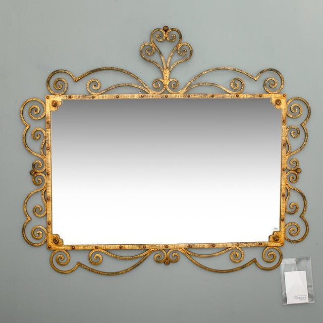 Mid century Italian mirror framed in a scrolled iron frame with a tall crest and gilded finish.