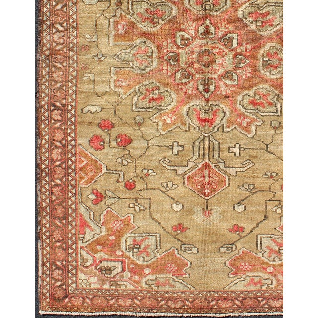 This vintage Persian rug features a large-scale, multicolored red and coral floral design complemented by a center...