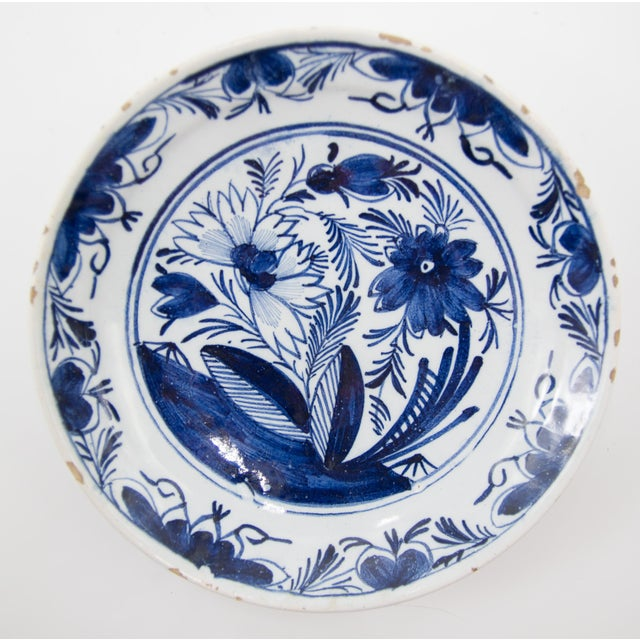 A gorgeous pair of antique 18th-Century Dutch Delft faience flower garden plates. These lovely plates have a hand painted...