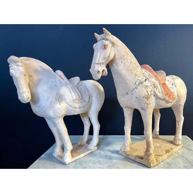 Pair of tang pottery horses. Roof tile manner, both left facing with matching scalloped saddle drapes (one broken and...
