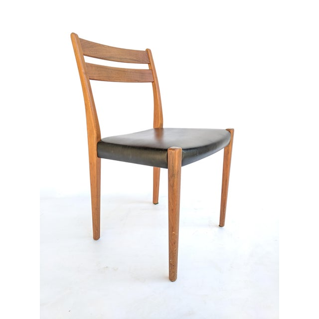 1960s teak dining or side chair by Svegards Markaryd. The chair has original black vinyl seat upholstery, and classic...