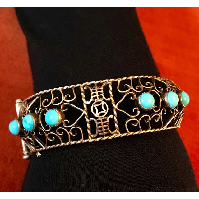 Circa 1930s to 1940s gold plated sterling silver, open work hinged bangle bezel set with 12 round turquoise cabochons. The...