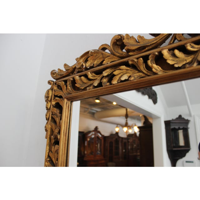 This ornate French gilt mirror was imported directly from France and dates to the early 20th century. It is made in a hard...