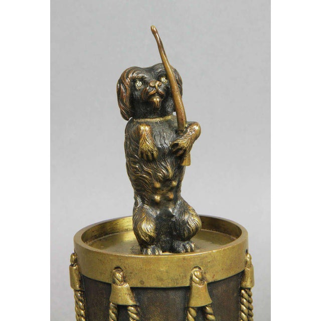 Dog with cut glass eyes holding a drum stick and seated on a drum.