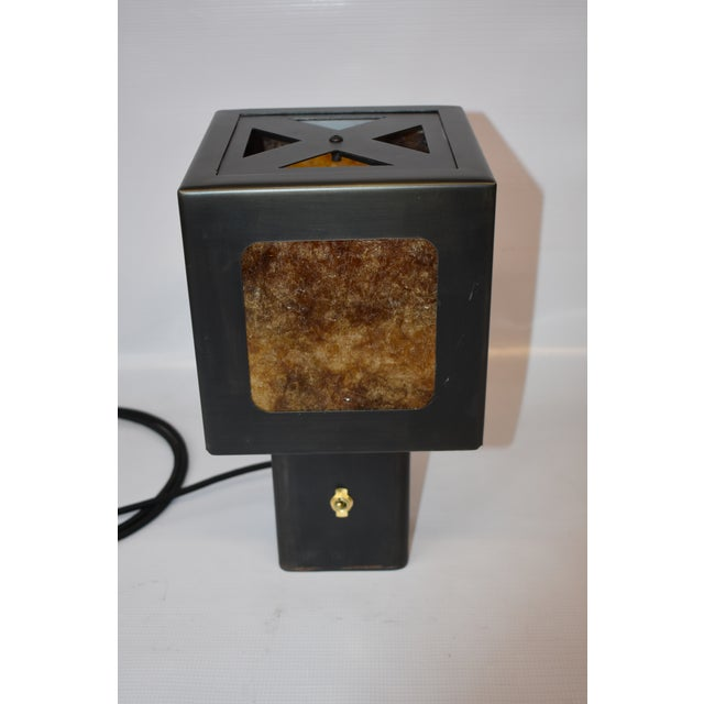 Blackened steel table lamp with amber mica paneling. Antique black patina finish with bronze accents. The idea for this...