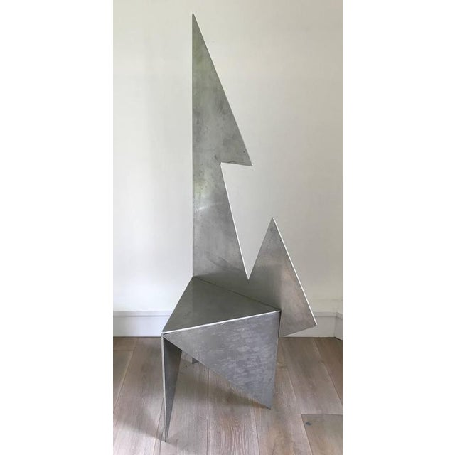 Interesting and unique cut steel chair with architectural form.
