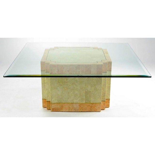 A derivation of art deco style, this coffee table has a square base with setback corners. The strong geometric form is...