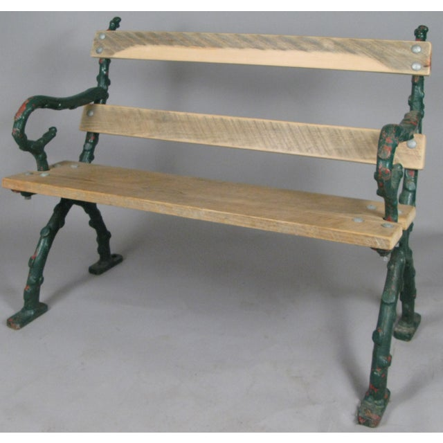 A very well made and handsome antique early 20th century garden bench from Bath, England. The cast iron frame is made in a...