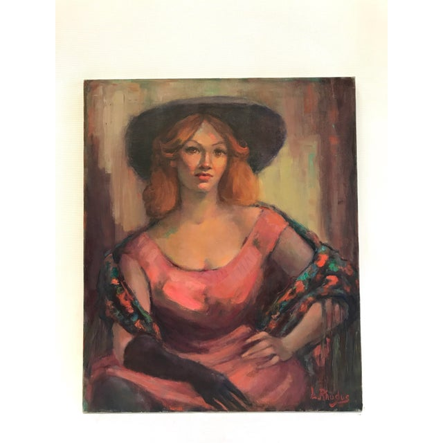 Signed portrait of a woman in pink by listed artist Lillian Rhodus (1906 - 1988). Artist has executed this oil on...