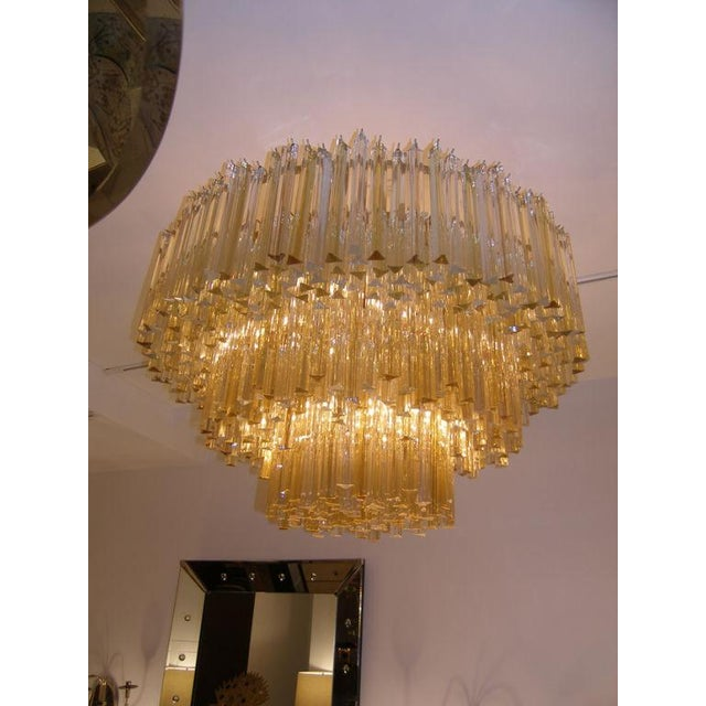 A three tiered chandelier consisting of multiple clear and amber crystals hanging from a brass frame with brass hardware...