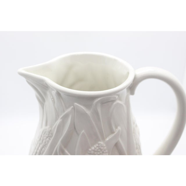 """Marked on the bottom with the maker's mark and """"Made in Italy"""" this vintage all-white majolica pitcher is large and with a..."""