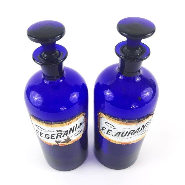 A set of two antique English cobalt blue apothecary bottles -- F.E.Gerani.Mac and F.E.Auranti -- fluid extract of geranium...