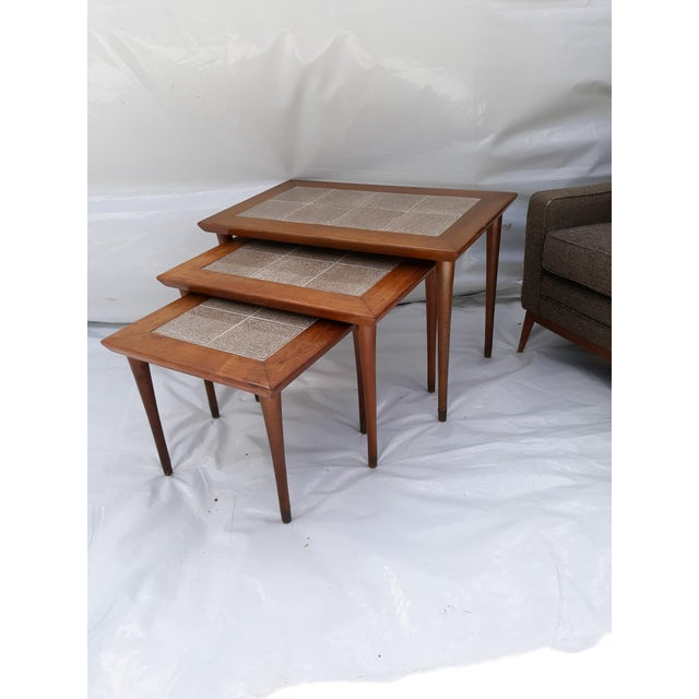 This is a fine quality set of 3 nesting tables. They are very heavy and i believe they are solid mahogany. They have tile...