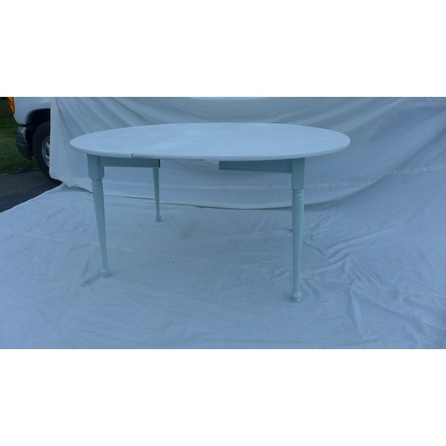 Vintage Heywood-Wakefield table painted in two colors. The top and legs are white, while the skirt is a sea breeze color....