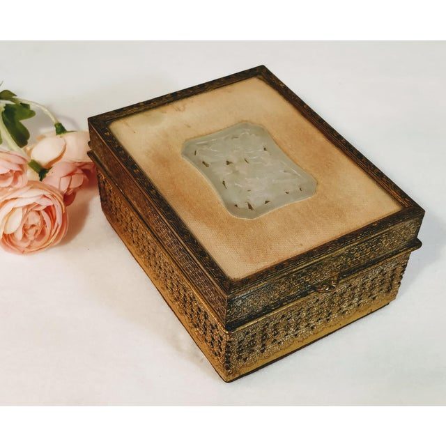 Stunning Chinese filigree gold gilt metal jewelry box with velvet lining and white carved jade insert. The jade is nestled...