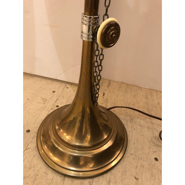 A wonderful elongated pair of brass table lamps inspired by musical horns having white enamel knobs, decorative chains, as...