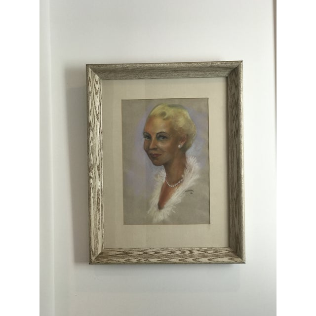 This is a portrait of a woman. It looks as though it was done with pastels. It is a portrait of a woman wearing pearl...