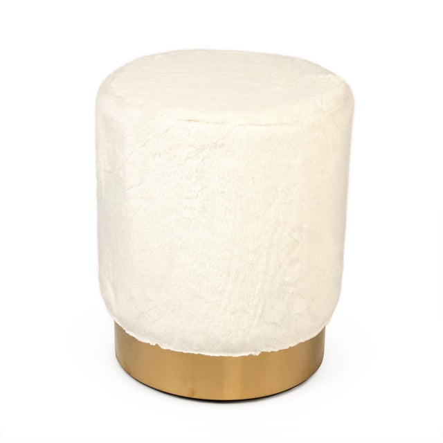 Cylindrical stool upholstered in white faux with stylish gold rim on bottom.