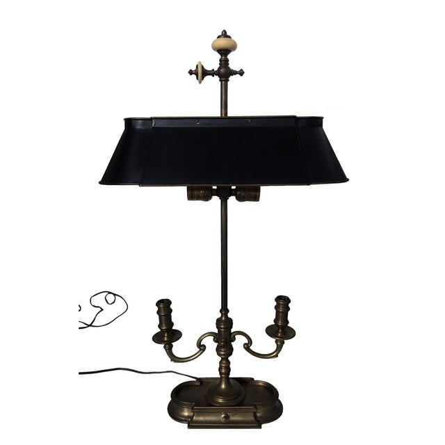 A French Bouillotte Lamp, consisting of two candlestick holders with a central non-flammable adjustable shade made of...