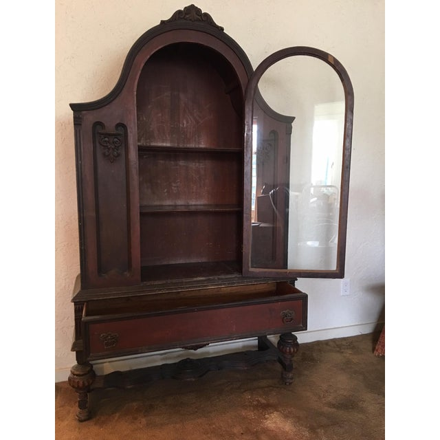 Selling a gorgeous antique book case (aka book shelf) with a curved top, glass door, storage drawers, and fine details.