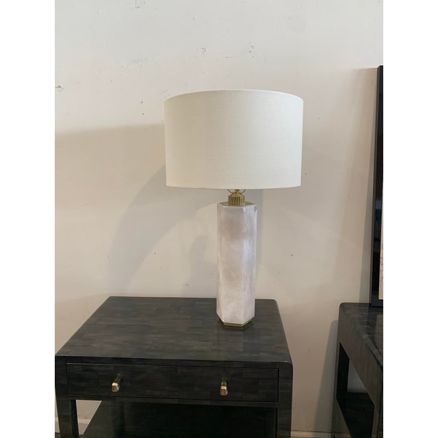 Substantial stone base lamp from Regina Andrew is made from alabaster and furnished with a brass toned base and white drum...