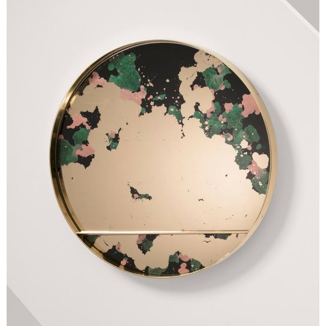 The Orbit Mirror by Emma Peascod is available in a variety of metals with a face available in four handmade verre eglomise...