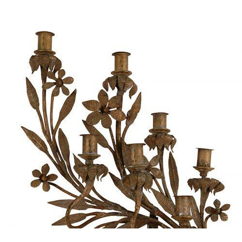 A large pair of hand forged iron candelabras with seven candle cups each. The gilding is painted and considerably toned...