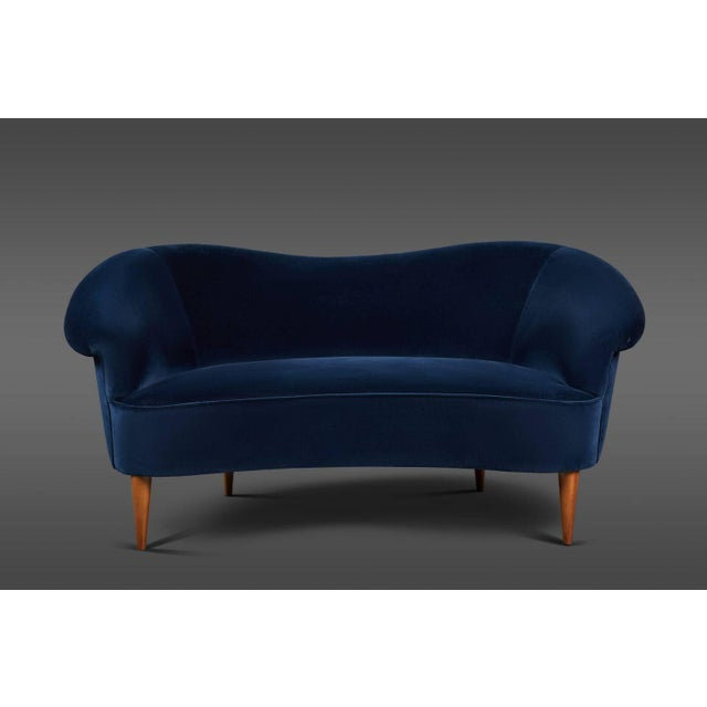 Elegant petite Italian blue velvet settee with conical wooden legs. Newly upholstered and truly lovely.