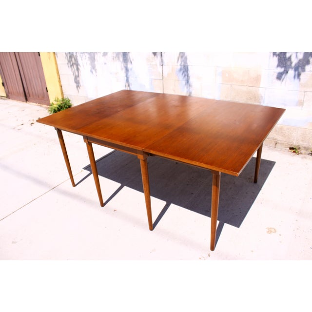 A stylish midcentury gateleg dining table by Henredon features a rich walnut finish, beautiful tapered legs, and a...
