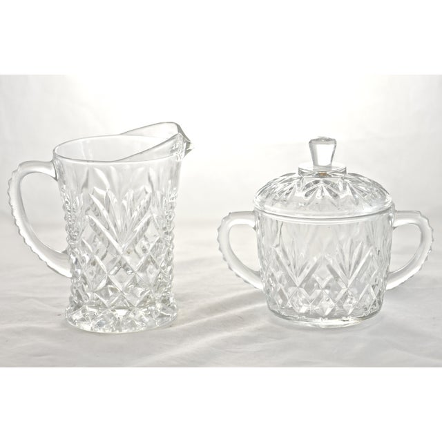 Large vintage sparkling faceted glass creamer and lidded sugar bowl in a pineapple pattern. No maker's mark. Dimensions:...