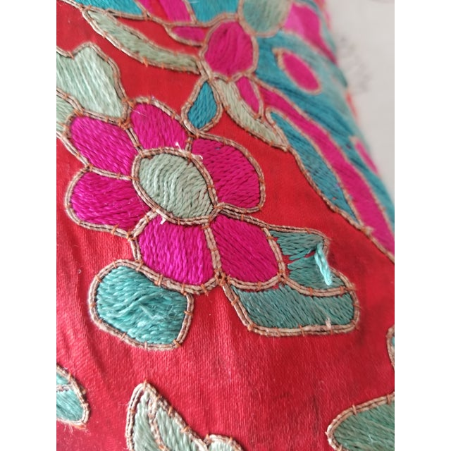 Exquisitely embroidered silk textile throw pillows, with silk ikat backs. Brilliant colors, heavy embroidery.
