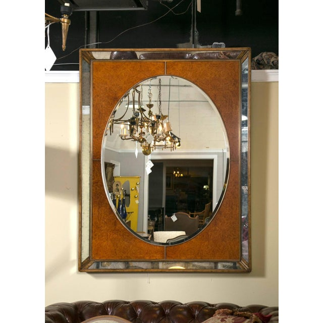 Monumental burl and glass Art Deco mirror. A burl frame encasing antiqued mirrored borders on the outset and gilt, and...