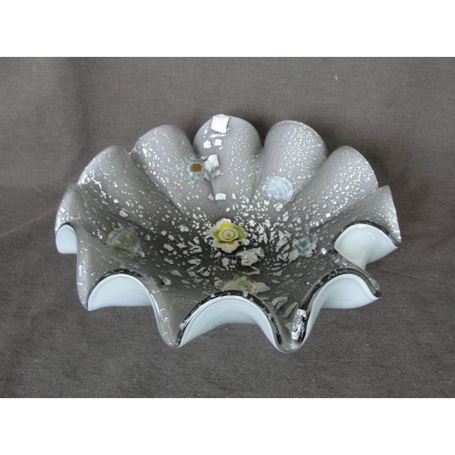 This is a beautiful studio art glass bowl with silver flakes and millefiori style flowers. The bottom layer is white from...