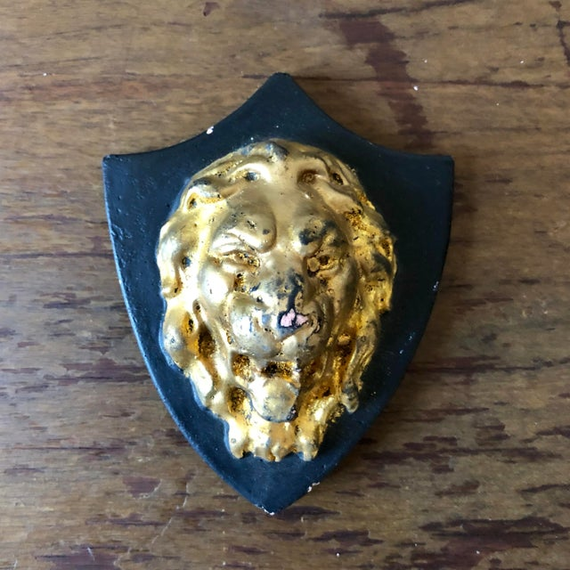 Set of six black and gold French plaster shield plaques, 5 with lion heads and one fleur de lis.