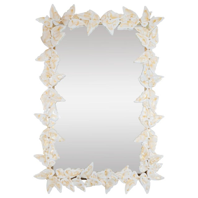 "Brass mirror with white Murano glass butterfly surround with ""brush stroke"" details."