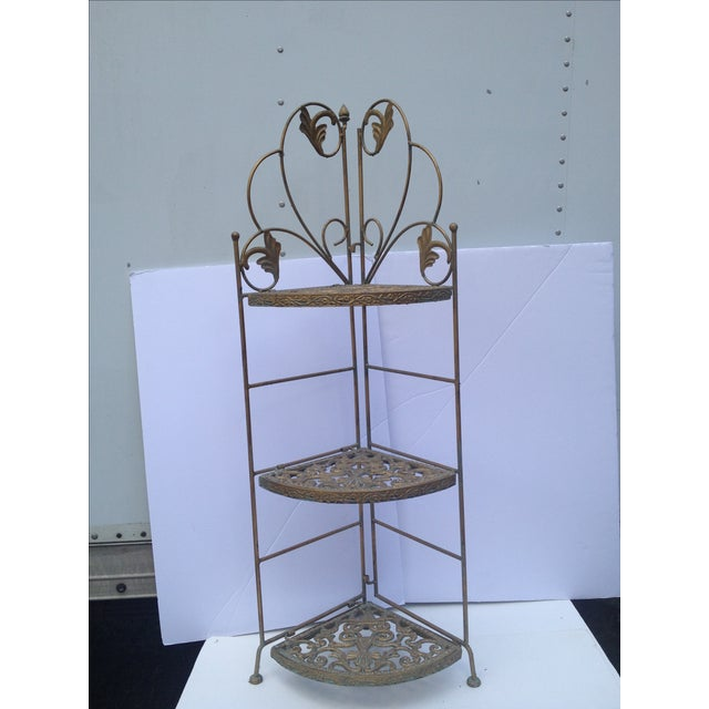 Decorative brass folding table has three shelves. When you drop the shelves down, the table folds in together for easy...