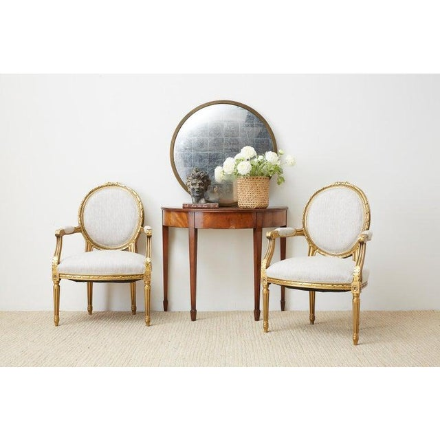 Lavish pair of French giltwood fauteuil armchairs hand carved in the Louis XVI taste. The beautiful frames have a round...