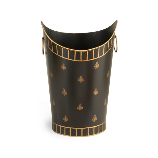 This is a wastebasket by Chelsea House Inc. The piece is hand painted black and gold with bee motifs.